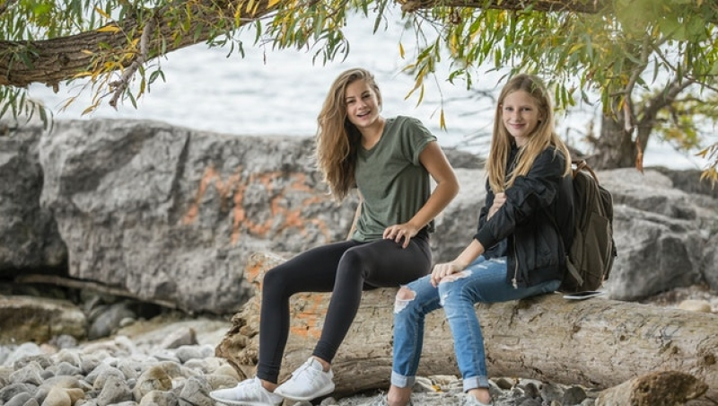 2-women-sitting-on-rock-during-daytime-214576